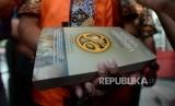 Buku yang digunakan untuk menutup tangan yang diborgol oleh tersangka kasus dugaan suap seleksi pengisian jabatan di Kementerian Agama Romahurmuziy usai menjalani pemeriksaan di Gedung KPK, Jakarta, Jumat (22/3).