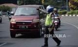 Petugas kepolisian mengamankan kendaraan roda empat di kawasan perluasan ganjil genap Jalan Majapahit, Jakarta, Senin (9/9/2019).