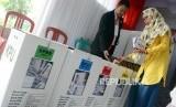 Sejumlah warga memasukan surat suara ke dalam kotak di TPS 30, Sawangan, Depok, Jawa Barat, Rabu (17/4).