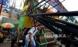 Warga berjalan menghindari instalasi kabel yang melintang di Jembatang Penyeberangan Orang (JPO) Margonda, Depok, Jawa Barat, Selasa (23/10).