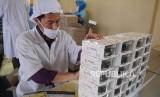 Seorang pekerja mengemas kue kering di pabrik kue kering Ina Cookies, di Jalan Bojongkoneng, Kota Bandung, Kamis (7/6).
