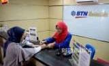 Petugas melayani transaksi nasabah di kantor layanan BTN Syariah, Jakarta, Senin (1/10).