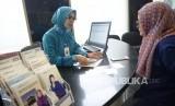 Petugas melayani transaksi nasabah di kantor layanan BCA Syariah, Jakarta, Senin (29/1).