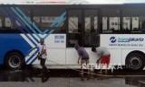 Sejumlah suporter Persija membersihkan bus Transjakarta di Kantor PT Transjakarta, Cawang, Jakarta, Kamis (13/12).