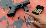 Petugas memperlihatkan senjata api beserta peluru yang akan digunakan pada uji balistik senjata api Glock 17 di lapangan tembak Mako Brimob, Kelapa Dua, Depok, Jawa Barat, Selasa (23/10).