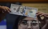 Petugas memeriksa mata uang dolar AS di salah satu tempat penukaran uang di Jakarta, Jumat (9/11).