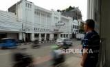 Warga menunggu bus dengan latar belakang diskotek Old City yang telah disegel di kawasan Kota Tua, Jakarta, Selasa (23/10).