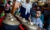 Anak-anak saat mencoba alat kesenian betawi pada acara Festival Warisan Budaya Tak Benda di kawasan Setu Babakan, Jakarta, Ahad (28/4).