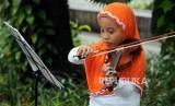 Anak-anak belajar memainkan alat musik biola di Taman Suropati, Menteng, Jakarta, Ahad (15/4).