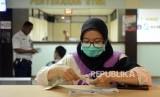 Warga mempersiapkan surat-surat saat melakukan pembayaran pajak kendaraan bermotor di Kantor Samsat Polda Metro Jaya, Jakarta, Jumat (16/11).