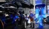 TAKSI LISTRIK. Awak armada e-Taxi Silver Bird memperagakan pengisian baterai mobil Tesla X75 di Port Charging Bluebird di Jakarta, Senin (22/4).