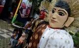 Pengunjung saat berfoto dengan ondel-ondel pada acara Festival Warisan Budaya Tak Benda di kawasan Setu Babakan, Jakarta, Ahad (28/4).