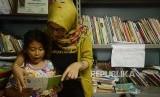 Anak-anak membaca buku dongeng di Sekolah Komunitas Jendela, Manggarai, Jakarta, Ahad (25/11).