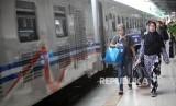 Penumpang berjalan saat akan menaiki kereta api di Stasiun Pasar Senen, Jakarta, Selasa (26/12).