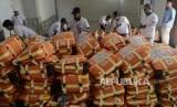 Sejumlah porter merapihkan koper calon jamaah haji di Asrama Haji Pondok Gede, Jakarta, Ahad (14/7).