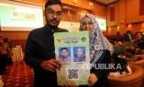 Pasangan suami istri menunjukan kartu nikahnya seusai peresmian Aplikasi Pencatatan Nikah (SIMKAH) Web dan Kartu Nikah di Auditorium Kementerian Agama, Jakarta, Kamis (8/11).