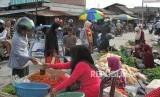 Pembeli melakukan transaksi dengan pedangan di pasar Impres Palu, Sulawesi Tengah, Sabtu (20/10).