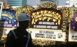 Sejumlah pelayat berjalan di depan karangan bunga ucapan belasungkawa atas wafatnya Presiden ke-3 Republik Indonesia BJ Habibie di rumah duka, kawasan Patra Kuningan, Jakarta, Kamis (13/9).