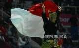 Pesilat Indonesia Sugianto mengibarkan bendera merah putih usai pertandingan cabang olahraga silat Asian Games 2018 kategori tunggal putra di Padepokan Pencak Silat TMII, Jakarta, Rabu (29/8).