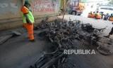 Petugas PPSU melihat motor yang hangus terbakar di kawasan slipi yang hangus terbakar pasca aksi demo pelajar tolak UU KPK hasil revisi dan RKUHP di kawasan Petamburan, Jakarta, Kamis (26/9/2019).