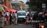 Warga bejalan didepan kendaraan angkutan kota (angkot) jurusan Tanah Abang yang melintas di Jalan Jatibaru, Tanah Abang, Jakarta, Ahad (4/2).