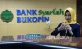 Karyawan melayani nasabah di Bank Syariah Bukopin (BSB), Jakarta,Senin (17/12).