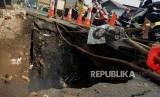 Pengendara motor melintas di dekat jalan yang amblas di Jalan Raya Sawangan, Depok, Jawa Barat, Jumat (28/6).