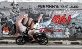 Pengendara melintas di depan mural bertema Pilkada serentak 2020 di kawasan Candi, Sidoarjo, Jawa Timur, Selasa (24/11/2020). Mural tersebut sebagai salah satu bentuk sosialisasi serta mendorong masyarakat untuk menggunakan hak suaranya dalam Pilkada serentak pada 9 Desember mendatang.