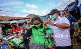 Petugas Kecamatan Pinang membagikan masker berbahan kain kepada sejumlah pengendara motor di Pinang, Kota Tangerang, Banten, Rabu (8/4) Pembagian masker tersebut merupakan tindak lanjut dari imbauan pemerintah untuk memakai masker saat beraktivitas di luar rumah guna mencegah penyebaran COVID-19
