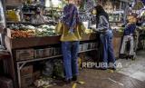 Sejumlah warga berdiri di lantai yang telah dipasang stiker panduan jarak saat berbelanja di  Kota Cimahi.  Dinas Kesehatan Kota Cimahi menyatakan ada empat kasus positif COVID-19 baru, dua di antaranya merupakan pedagang di Pasar Antri Kota Cimahi.