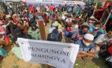 Sejumlah pengungsi etnis Rohingya duduk menunggu saat tiba di tempat penampungan yang baru di Balai Latihan Kerja (BLK) Desa Mee Kandang, Lhokseumawe, Aceh, Jumat (10/7/2020). Sebanyak 99 orang pengungsi Rohingya yang terdiri dari 43 orang dewasa dan 56 anak-anak dipindahkan ke tempat penampungan sementara yang baru dan sehat sambil menunggu kepastian dari imigrasi, IOM dan UHNCR soal sampai kapan mereka akan berada di Indonesia.