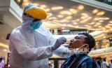 Petugas mengambil sampel lendir dari seorang pengunjung saat tes swab COVID-19 di salah satu pusat perbelanjaan modern di Kota Semarang, Jawa Tengah, Rabu (20/05/2020). Tes yang dilakukan Satgas Percepatan Penanganan COVID-19 Kota Semarang secara acak terhadap ratusan pengunjung maupun karyawan pada pusat perbelanjaan modern itu untuk mengetahui kesehatan mereka dalam upaya mendeteksi serta mencegah penyebaran virus Corona (COVID-19) di tengah lonjakan pengunjung jelang lebaran
