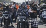 Anggota satuan pengamanan adat Bali atau Pecalang memeriksa surat jalan seorang pengendara saat hari pertama penerapan Pembatasan Kegiatan Masyarakat (PKM) di pos pantau perbatasan Biaung, Denpasar, Bali, Jumat (15/5/2020). Kota Denpasar menerapkan PKM selama satu bulan dengan mendirikan 10 pos pantau terutama di perbatasan kota untuk mengawasi aktivitas warga tanpa tujuan jelas dan melanggar protokol kesehatan termasuk melanggar larangan mudik dalam upaya menghentikan penyebaran wabah COVID-19