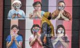 Warga melintas di dekat mural bergambar simbol orang berdoa menggunakan masker yang mewakili umat beragama di Indonesia di kawasan Juanda, Kota Depok, Jawa Barat, Kamis (18/6/2020). Mural yang dibuat oleh warga itu bertujuan untuk memberikan edukasi kepada masyarakat untuk menggunakan masker sebagai salah satu  pencegahan dan penyebaran Covid-19