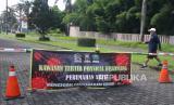 Seorang warga melintas di depan portal jalan yang ditutup di Perumahan Araya, Malang, Jawa Timur, Senin (30/3/2020). Sejumlah perumahan di kawasan tersebut mulai menutup akses jalan untuk mencegah penyebaran virus Corona