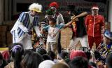 Anggota Badut Nyentrik Cimahi Bandung Sauyunan (Necis) menghibur anak-anak korban bencana tanah longsor di posko pengungsian, Desa Cihanjuang, Kecamatan Cimanggung, Kabupaten Sumedang, Jumat (22/1/2021).