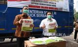 Menteri Sosial Juliari Batubara (kiri) menyerahkan bantuan alat pelindung diri (APD) untuk tenaga medis kepada Menteri BUMN Erick Thohir (kanan) di Gedung Kementerian BUMN, Jakarta, Selasa (7/4/2020). Kementerian Sosial memberikan bantuan sebanyak 20 ribu pakaian APD kepada Kementerian BUMN guna membantu tenaga medis dalam penanganan COVID-19