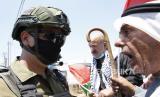 Pemrotes Palestina berdebat dengan tentara Israel ketika mereka mencoba untuk mencapai tanah mereka selama demonstrasi menentang rencana Israel untuk mencaplok bagian-bagian Tepi Barat yang diduduki di desa Hares dekat kota Salfit di Tepi Barat utara, 24 Juli 2020. Palestina masih bergulat dengan kasus Covid-19 di tengah konfliknya dengan Israel.