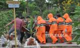 Medan Siapkan Pemakaman Khusus Jenazah Covid-19. Petugas penggali kubur menggunakan alat pelindung diri (ADP) bersama kerabat keluarga memakamkan Pasien Dalam Pengawasan (PDP) Covid-19 di Medan, Sumatra Utara.
