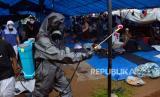Anggota kepolisian Polda Sulsel menyemprotkan cairan di lokasi kegiatan Ijtima Ulama Asia di Desa Pakkatto, Kecamatan Bontomarannu, Kabupaten Gowa, Sulawesi Selatan, Kamis (19/3/2020).