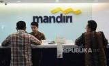 Petugas melayani nasabah di Bank Mandiri KC Pasar Rebo, Jakarta, Rabu (20/6).