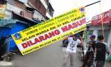 Warga melintas di depan pintu masuk yang melakukan karantina wilayah Di Cipulir, Jakarta Selatan, Rabu (8/4/2020). Karantina wilayah tersebut dilakukan oleh warga guna mencegah penyebaran Virus Corona (COVID-19) serta membantu Pemrov DKI dalam menerapkan status Pembatasan Sosial Bersekala Besar (PSBB)