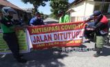 Warga memasang portal di akses masuk Desa Gogorante, Kediri, Jawa Timur, Sabtu (23/5/2020). Sejumlah desa di Kediri menutup akses masuk wilayahnya untuk mengantisipasi warga luar desa berkunjung saat lebaran guna menangkal penyebaran COVID-19