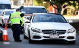 Seorang perwira polisi mengarahkan mobil untuk pemeriksaan lebih lanjut di sebuah pos pemeriksaan di perbatasan negara bagian Queensland-New South Wales di Coolangatta di Gold Coast, Queensland, Australia, 01 Juli 2020. Queensland akan membuka perbatasannya dengan semua negara bagian dan teritori lain, kecuali Victoria, pada 10 Juli.