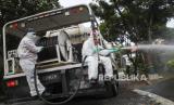 Petugas mengenakan pakaian pelindung saat menyemprotkan disinfektan. (Ilustrasi)