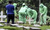 Petugas pemakaman menurunkan peti jenazah pasien COVID-19 di TPU Pondok Ranggon, Jakarta, Senin (30/3/2020). Juru bicara pemerintah untuk penanganan COVID-19 Achmad Yurianto per Senin (30/3/2020) pukul 12