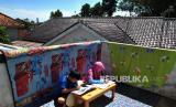 Siswa SD mengerjakan tugas sekolah menggunakan aplikasi daring dari gawai sambil berjemur sinar matahari pagi di rumahnya di Laladon Gede, Desa Laladon, Ciomas, Kabupaten Bogor, Jawa Barat, Selasa (31/3/2020). Kebijakan belajar, bekerja, dan beribadah dari rumah diharap bisa memperat hubungan keluarga.