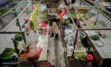 Pedagang melayani pembeli di balik tirai plastik di Pasar Bandeng, Kota Tangerang, Banten, Selasa (2/6). Pengelola pasar Bandeng mewajibkan pedagang untuk memasang tirai plastik sebagai antisipasi penyeberan COVID-19