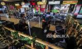 Pekerja melayani pengunjung di meja yang dipasangi pembatas plastik pada salah satu restoran di Bekasi, Jawa Barat, Ahad (7/6). Pembatas plastik itu dipasang untuk menjaga pembatasan jarak fisik antar pengunjung yang merupakan bagian dari penerapan protokol kesehatan di era new normal