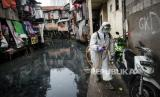 Petugas Palang Merah Indonesia (PMI) Jakarta Pusat menyemprotkan cairan disinfektan di pemukiman padat penduduk  di kawasan Kebon Melati, Jakarta, Sabtu (28/3). Penyemprotan yang dilakukan di tiga kelurahan diantaranya Kelurahan Kebon Melati, Kelurahan Petamburan, Kelurahan Kebon Kacang sebagai upaya mengantisipasi penyebaran virus corona COVID-19 di area tersebut